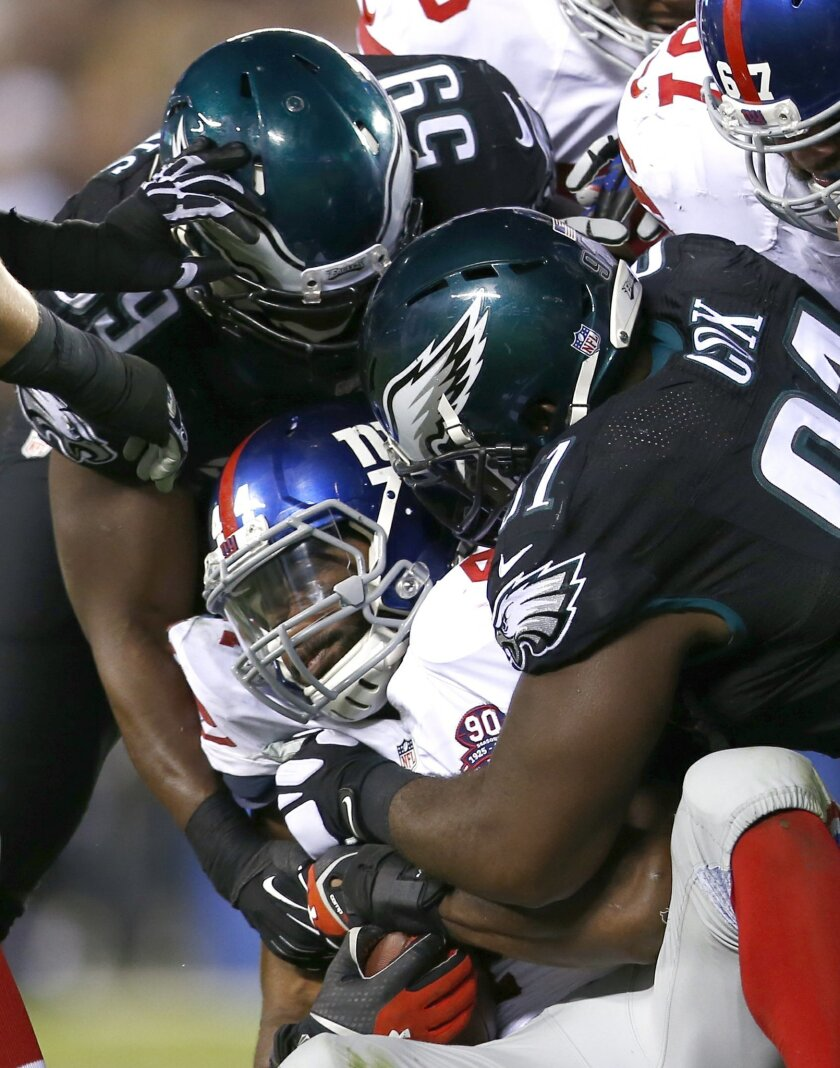 New York Giants running back Andre Williams, center, is tackled between Philadelphia Eagles inside linebacker DeMeco Ryans, left, and defensive end Fletcher Cox during the second half of an NFL football game, Sunday, Oct. 12, 2014, in Philadelphia. (AP Photo/Matt Rourke)