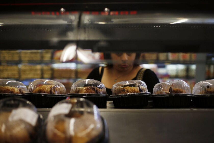 In this Sept. 2, 2015, photo, a woman looks at shelves of roasted chickens at a Wal-Mart Lider hypermarket in Santiago, Chile. As Wal-Mart tries to build an international juggernaut, it has had no greater success than in Chile, where even its failures show a commitment to adapting quickly to local