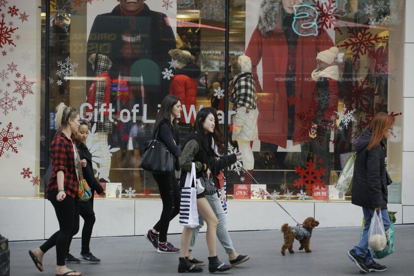 FILE - In this Sunday, Nov. 22, 2015, file photo, shoppers walk in front of a holiday display in San Francisco. A lack of must-have items, big discounts on winter clothes and pricey toys are defining this year's holiday season. (AP Photo/Marcio Jose Sanchez, File)