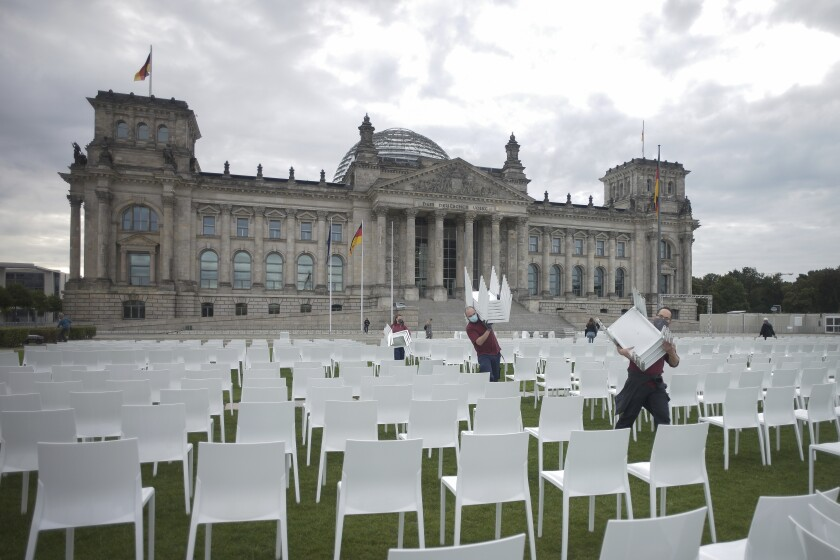 Activists place chairs as part of a protest against racism and for the admission of more migrants by the European Union in front of the Reichstags building in Berlin, Germany, Monday, Sept. 7, 2020. (AP Photo/Markus Schreiber)