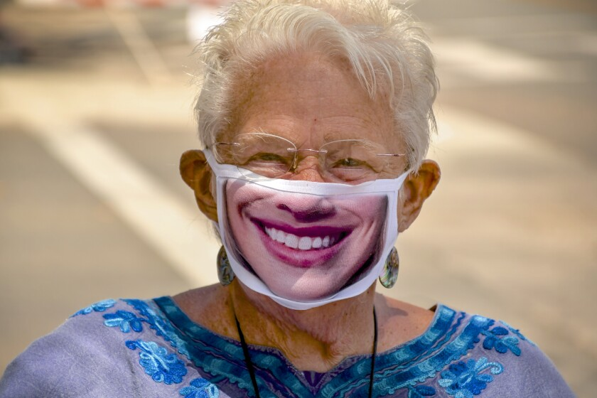 Santa Barbara has banned cars from part of State Street. Ruth Marshall,  who backs the change, sports a mask bearing a smile.