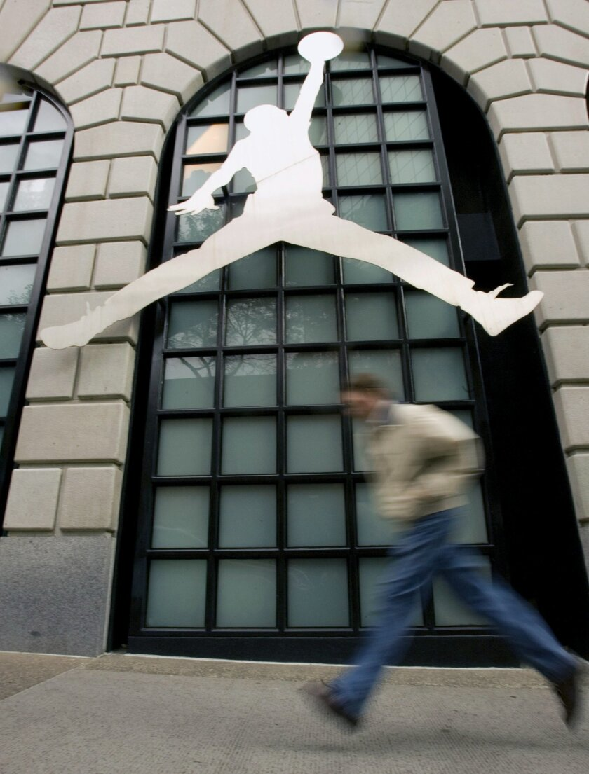 FILE - In this Sept. 29, 2009 file photo, a pedestrian runs past the famous Nike Air Jordan logo in front of the Niketown store in downtown Portland, Ore.  A photographer has accused Nike of violating the copyright of his 1984 image of a soaring Michael Jordan, which he alleges the company later mi