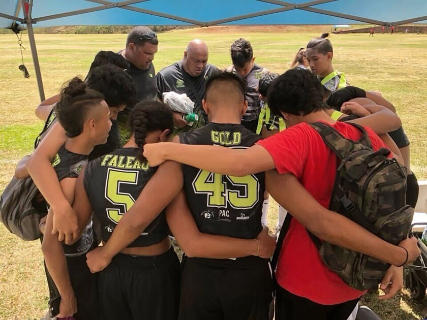 This 2017 photo provided by Ke'ala Aki shows Willie Talamoa, rear center with shaved head, next to Kanohi Aki, rear left, as they pray with players from their 15-and-under flag football team in Honolulu. A Honolulu community is mourning the loss of Talamoa, a mentor, football coach and father figure who died after contracting COVID-19. (Ke'ala Aki via AP)
