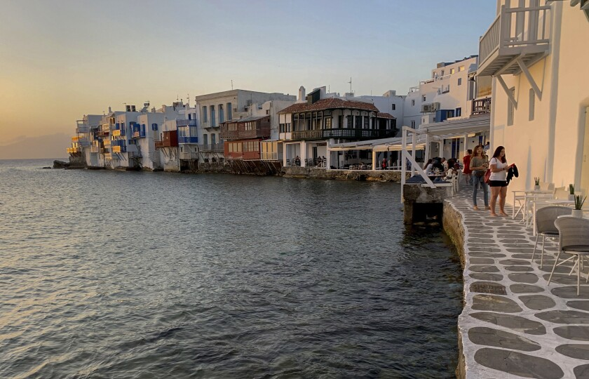 In this Tuesday, June 9, 2020 photo, visitors sit in bars in an area known as Little Venice on the Greek island of Mykonos. Business owners and locals officials on the Greek holiday island of Mykonos, a popular vacation spot for celebrities, club-goers, and high rollers, say they are keen to reopen for business despite the risks of COVID-19 posed by international travel. Greece will officially launch its tourism season Monday, June 15, 2020 after keeping the country's infection rate low. (AP Photo/Derek Gatopoulos)