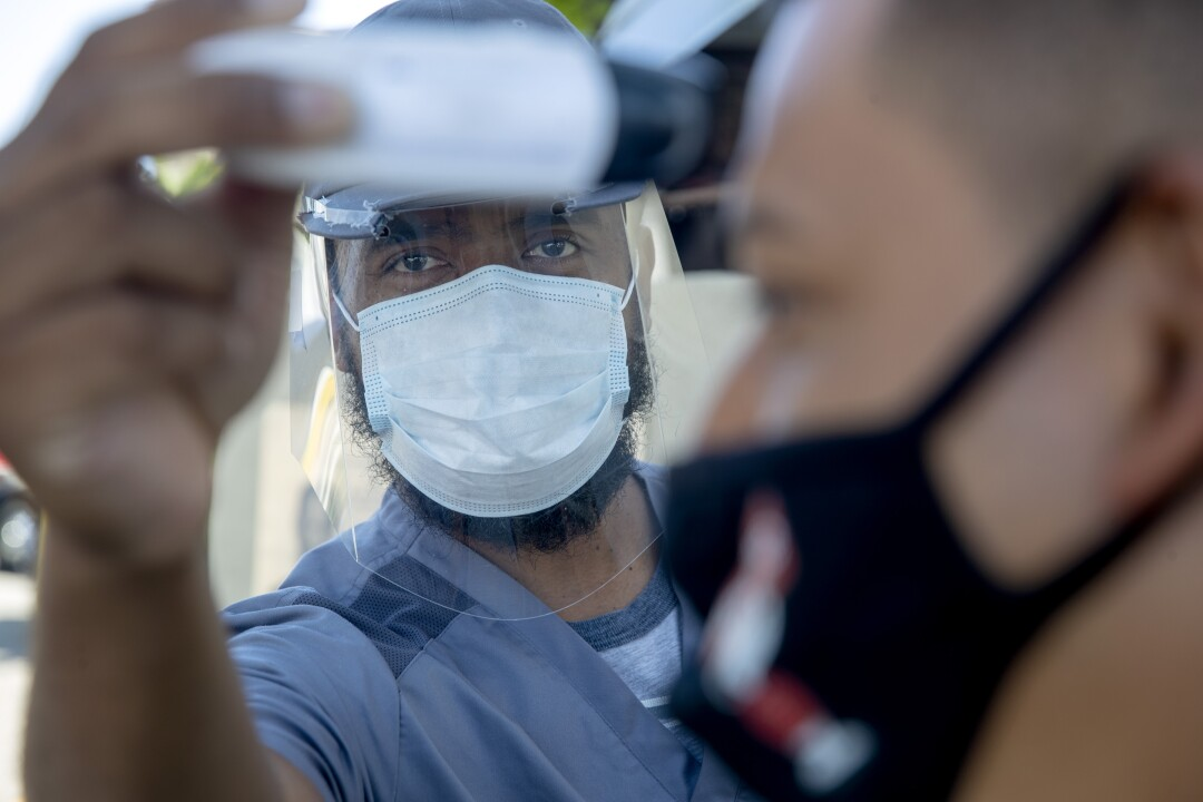Nurse Bobby Binissa, wearing a mask and a plastic face shield, takes the temperature from a patient's forehead
