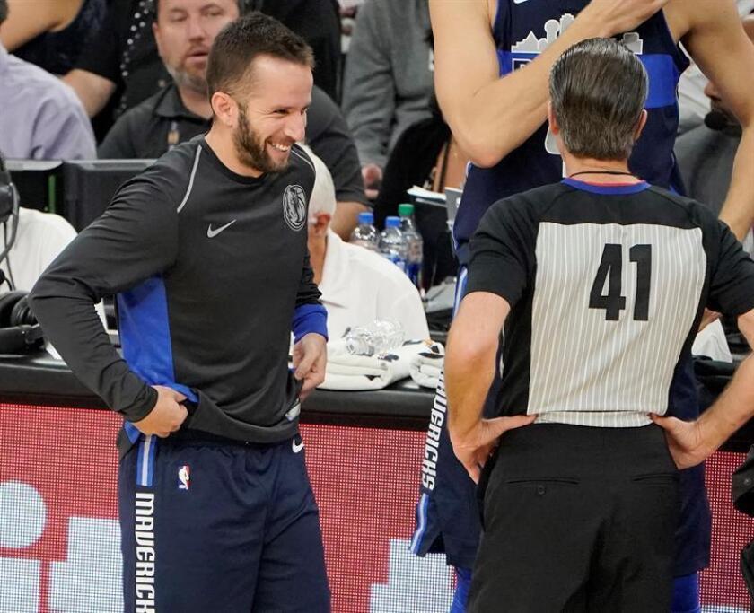 Jose Juan Barea (i) de los Dallas Mavericks se ríe con un árbitro durante un partido de baloncesto de la NBA. EFE/Archivo