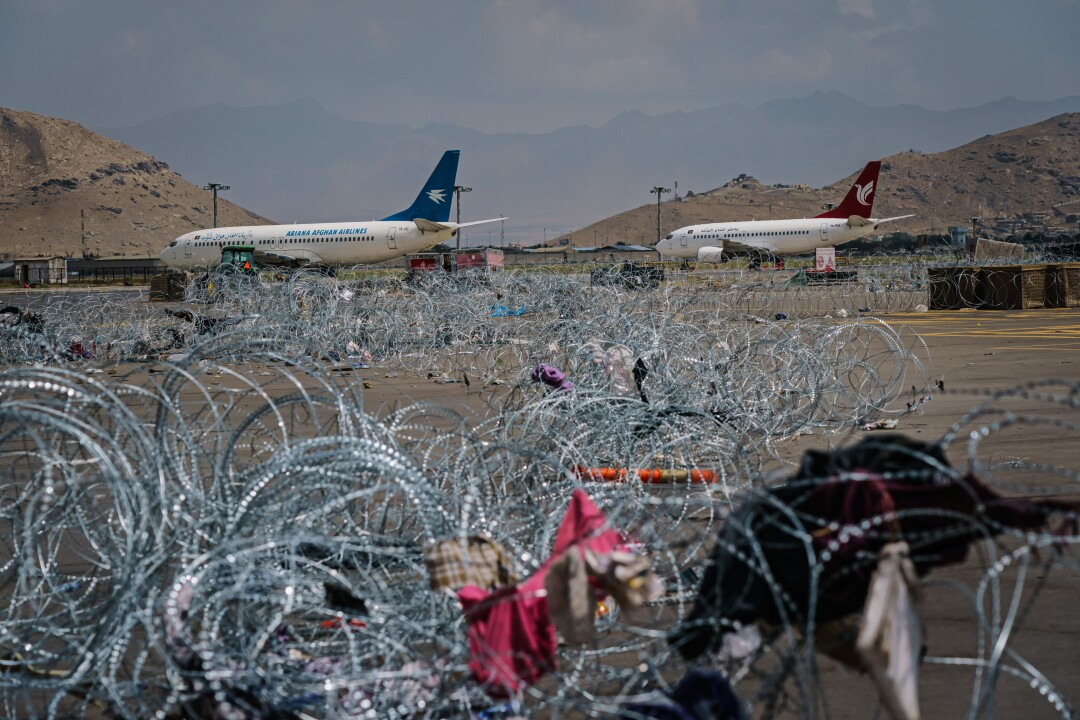 Barbed wire covers the ground with jetliners in the background