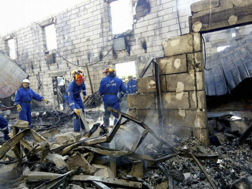 In this Sunday, May 29, 2016 photo, supplied by the Ukrainian Emergency Situations Ministry Press Service, emergency ministry employees search a site of a fire at Litchi, Kiev region, Ukraine. Ukraine's emergency services say a fire has swept through a private home for the aged, killing over a dozen of the 35 residents and injuring five others. No cause has yet been determined for the fire that broke out early Sunday in Litochki, a village 42 kilometers (25 miles) north of Kiev, the capital. (Ukrainian Emergency Situations Ministry Press Service Photo via AP)