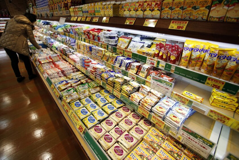 In this Tuesday, Dec. 9, 2014 photo, a shopper chooses dairy products as the shelf selling butter, right, is almost empty at a supermarket in Tokyo. Worsening butter shortages are a symptom of deeply entrenched resistance to reforms Prime Minister Shinzo Abe will be struggling to deliver even if hi