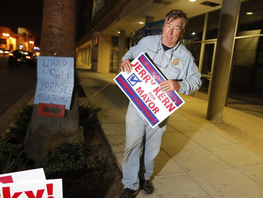 Oceanside city councilman and then mayoral candidate Jerry Kern removes his election signs along Coast Highway in Oceanside after an unsuccessful bid for mayor in 2012. On Tuesday, Kern announced he's abandoning a campaign for Assembly.
