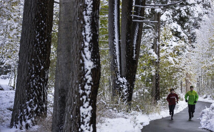 A couple run on a trail after a fall Sierra Nevada storm dropped nearly a foot of snow at Mammoth Mountain and less in town in Mammoth Lakes.