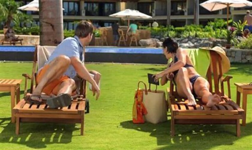 This image from video shows an image from a Kindle Paperwhite commercial featuring a young woman on a beach vacation lounging next to a young man, waiting for their husbands, shown in the background at the bar. Welcome to the latest in gay imagery in mainstream advertising, where LGBT people have been waiting for a larger helping of fairness and accuracy, on screen and in print. Traditionally lagging behind TV and film content in terms of LGBT inclusion, advertisers in this country are sufferin