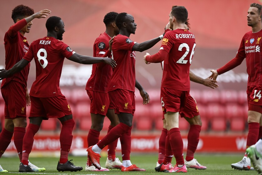 Liverpool's Sadio Mane, center, celebrates after scoring the opening goal during the English Premier League soccer match between Liverpool and Aston Villa at Anfield Stadium in Liverpool, England, Sunday, July 5, 2020. (Shaun Botterill/Pool via AP)