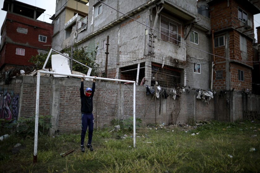 Nicolas Suarez, 16, poses for a photo as he hangs from a soccer goalpost in a soccer field that's closed due to the COVID-19 lockdown in the Fraga neighborhood of Buenos Aires, Argentina, Saturday, June 6, 2020. Suarez, who is recognized as one of the best players in his neighborhood, said that even though he's afraid of the virus he needs to keep playing, as he has aspirations to go professional. (AP Photo/Natacha Pisarenko)