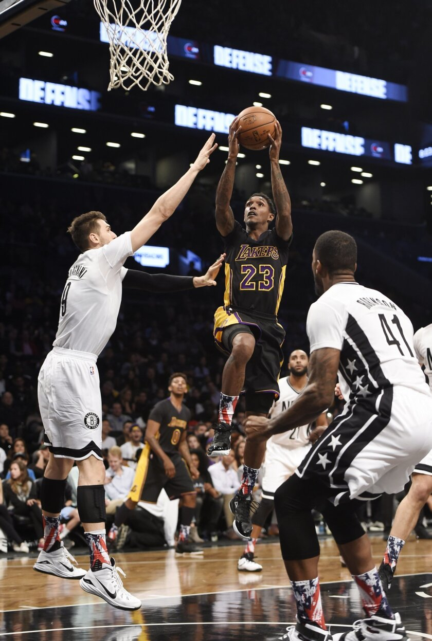 Los Angeles Lakers guard Lou Williams (23) goes up for a basket between Brooklyn Nets center Andrea Bargnani (9) and forward Thomas Robinson (41) during the first half of an NBA basketball game Friday, Nov. 6, 2015, in New York. (AP Photo/Kathy Kmonicek)