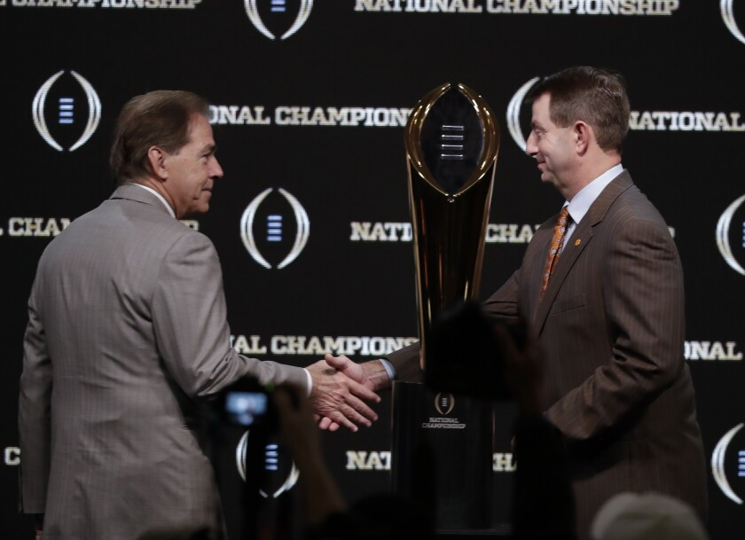 Alabama head coach Nick Saban and Clemson head coach Dabo Swinney pose with the trophy at a news conference for the College Football Playoff championship game on Jan. 6 in Santa Clara.