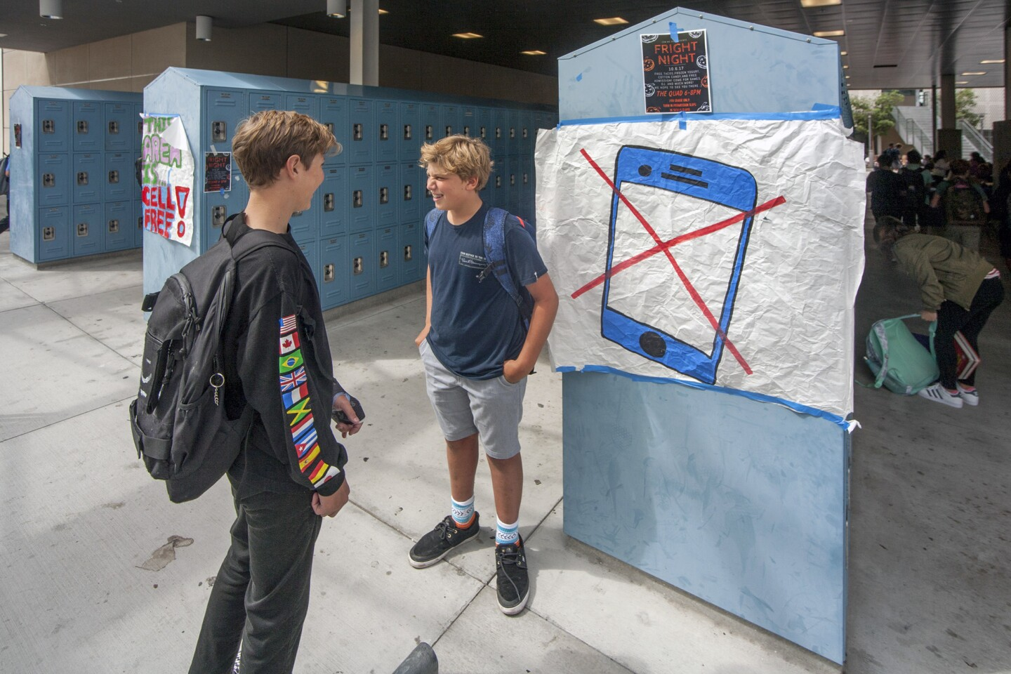 Students Jack Bunting and Jack Rees socialize at Corona del Mar Middle School beside signs designating a cellphone-free area.