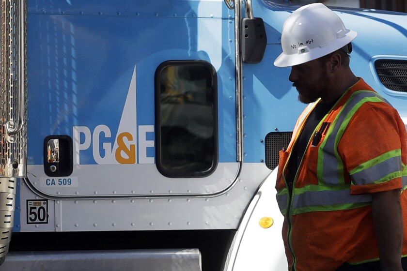 A Pacific Gas & Electric worker walks in front of a truck in San Francisco.