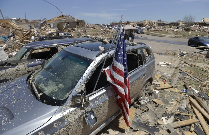 An American flag sits in a destroyed car's window in a neighborhood devastated by the tornado that ripped through Moore, Okla., on Monday