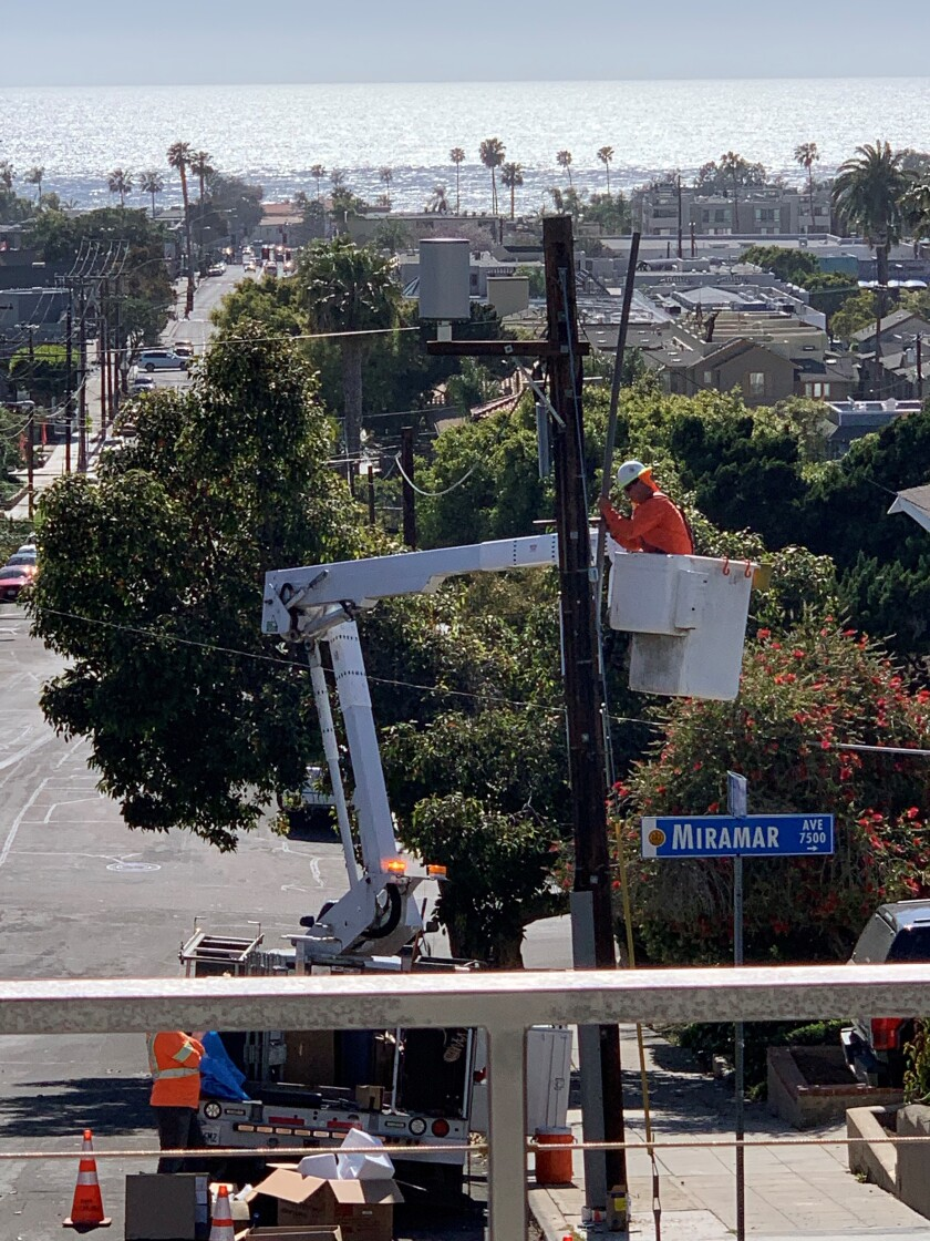 AT&T employees install a 5G miniature tower on a pole in front of La Jolla resident Harris Cohen's house.