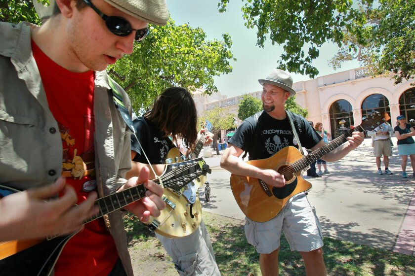 Ian Trahan, left, of San Diego plays mandolin while son-father duo Jimmy Bortree and Tim Bortree of Rancho Santa Fe, play guitar during a rendition of the Beatles' A Hard Day's Night at one of several Mass Appeal events during Make Music Day in Balboa Park.