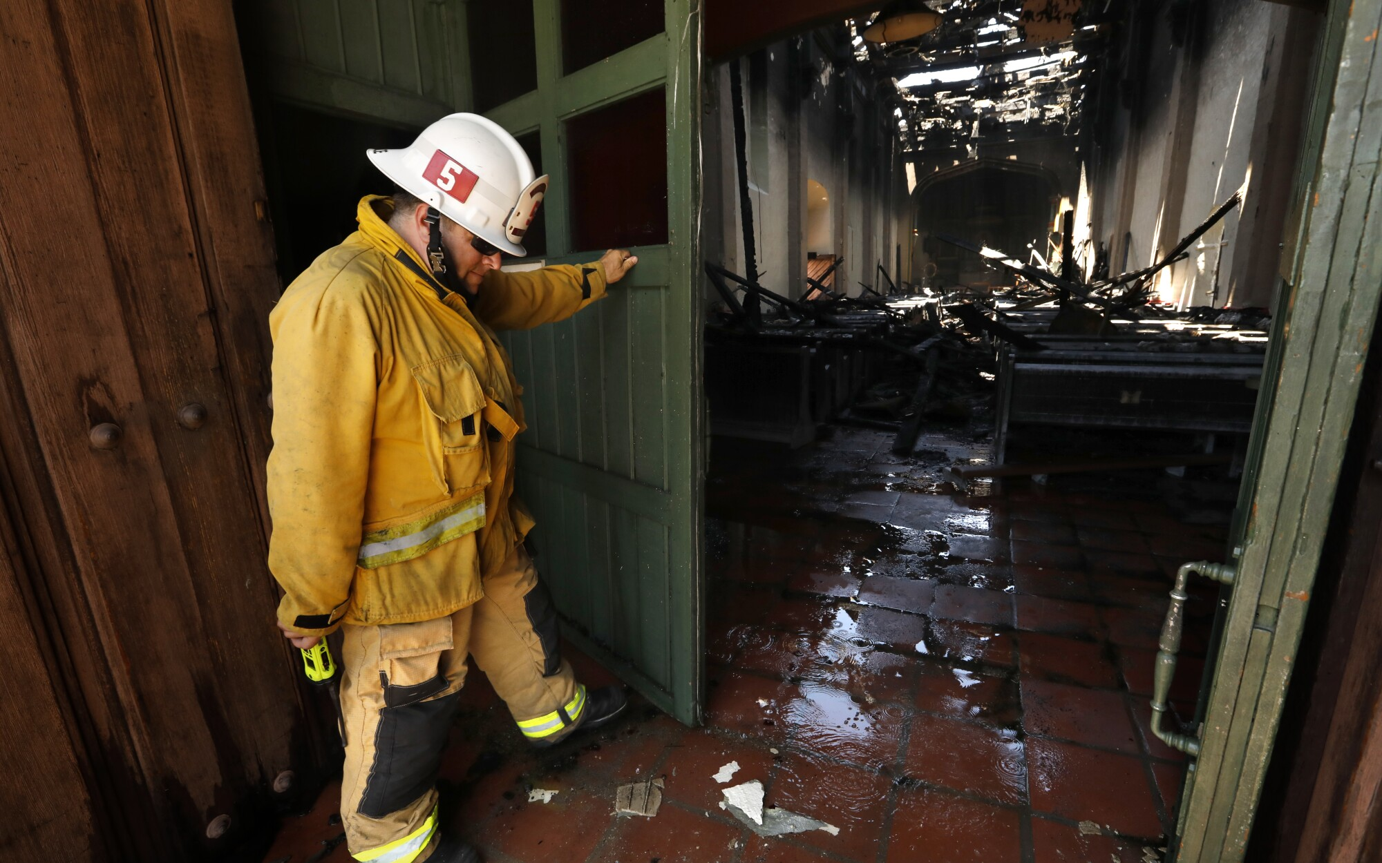 San Gabriel Fire Captain David Mulligan opens a door to the burned and severely damaged interior of the San Gabriel Mission