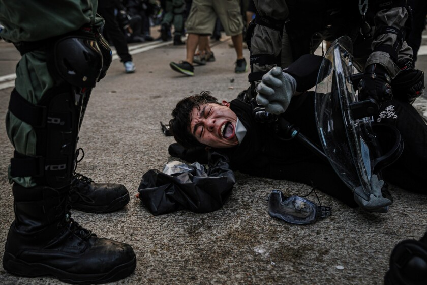 Police officers in riot gear pin down young female demonstrators near the HK Police Headquarters during the protest in Hong Kong.
