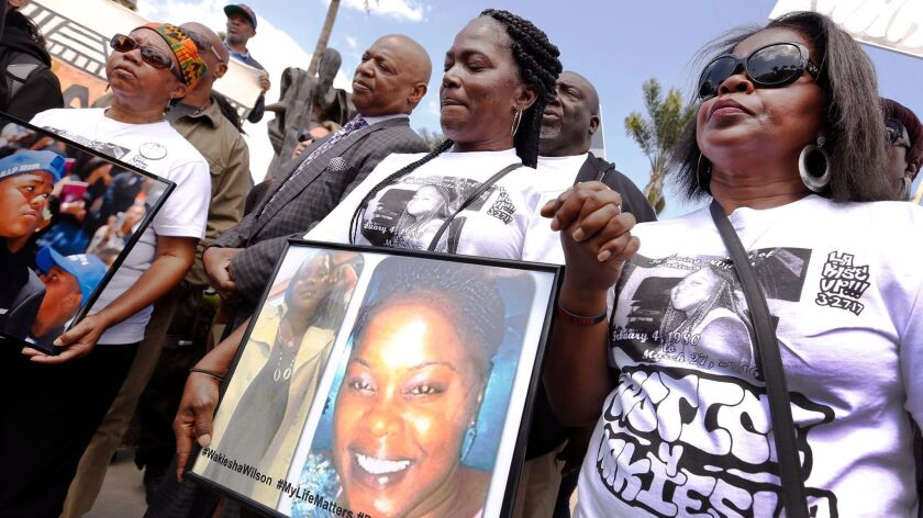 Lisa Hines holds a photo of her daughter, Wakiesha Wilson, during a rally in Watts a year after Wilson's 2016 death in an LAPD jail cell.