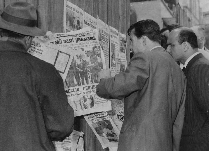 Citizens standing at a newsstand read of the capture of Prime Minister Adnan Menderes after a military coup, in Istanbul, Turkey, May 28, 1960. (AP Photo)