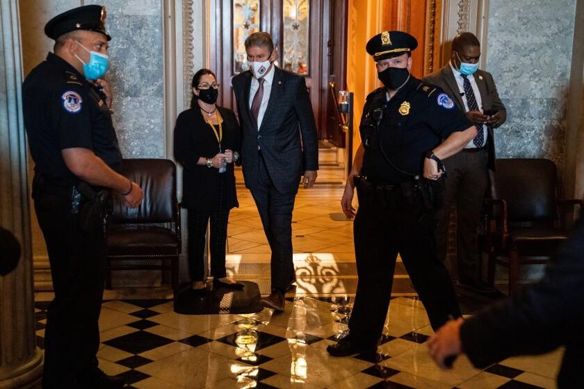 سناتور جو مانچین در سالن های کنگره قدم می زند