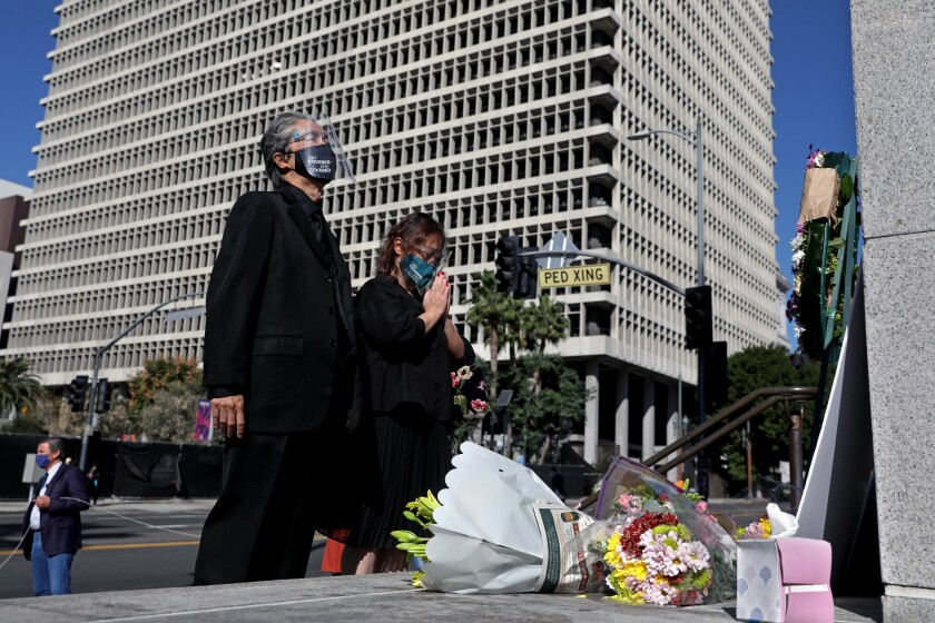 A court interpreter, left, and his significant other attend a vigil outside Los Angeles Superior Court.