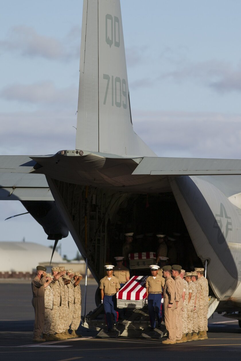 U.S. Marines unload the remains of 36 unidentified Marines found at a World War II battlefield during a ceremony at Joint Base Pearl Harbor-Hickam, Sunday, July 26, 2015, in Honolulu. A Florida-based private organization called History Flight recovered the remains from the remote Pacific atoll of Tarawa. (AP Photo/Marco Garcia)