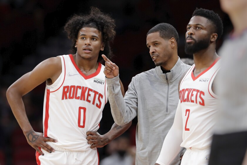 Houston Rockets head coach Stephen Silas, center, talks with guard Jalen Green (0) and forward David Nwaba (2) during a time out during the first half of an NBA basketball game against the Washington Wizards Tuesday, Oct. 5, 2021, in Houston. (AP Photo/Michael Wyke)