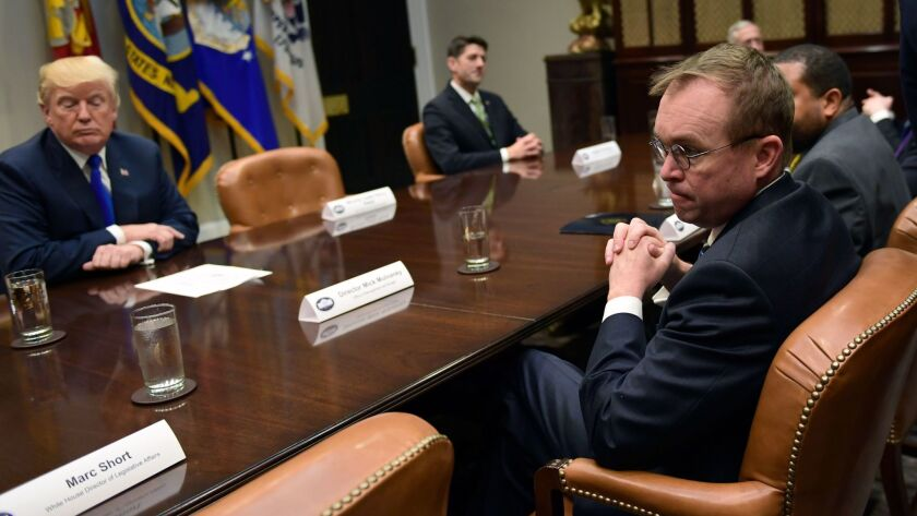White House budget director Mick Mulvaney, right, attends a meeting with President Trump in Washington on Nov. 28.