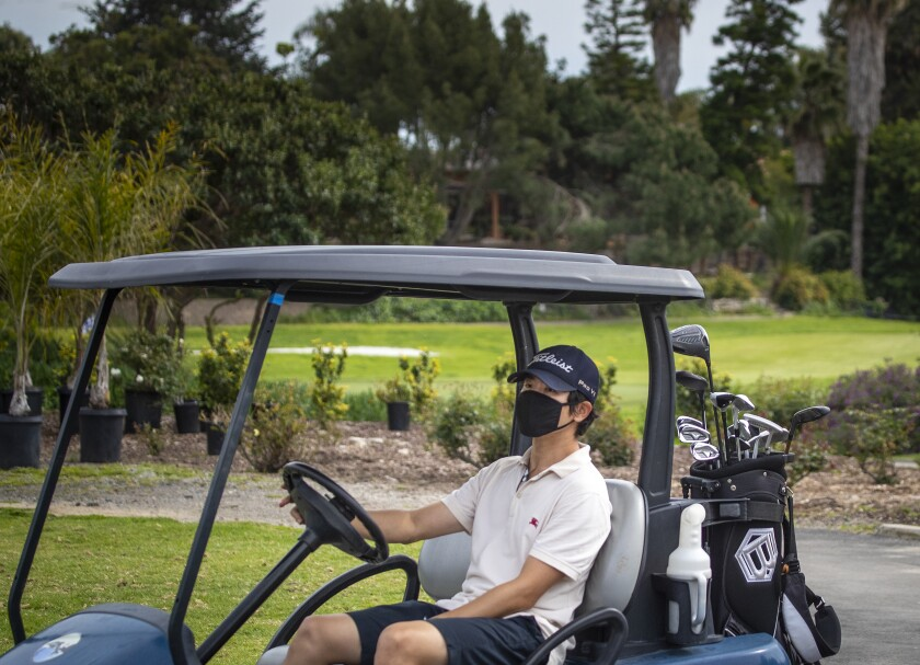 A golfer wears a protective mask while driving the golf cart