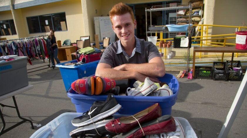Christian Moyer, a senior at University City High School, stands next to several containers of shoes he has collected from friends and family to donate for the homeless served by the San Diego Rescue Mission.