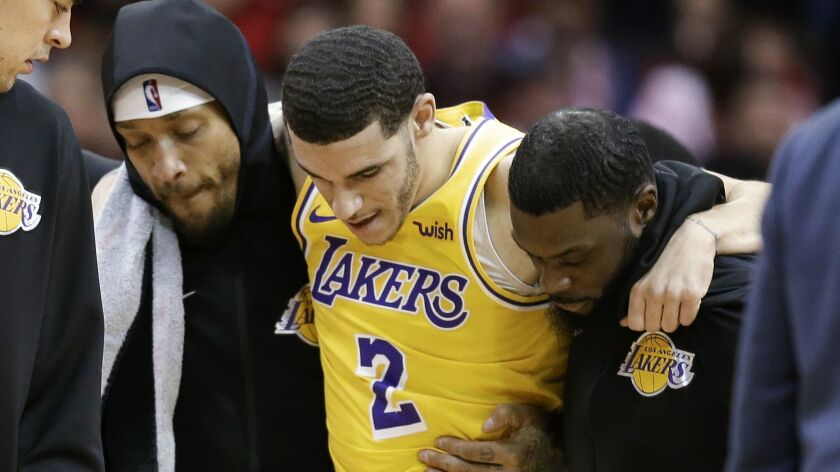 Los Angeles Lakers guard Lonzo Ball (2) is carried off the court by Michael Beasley, left, and Lance