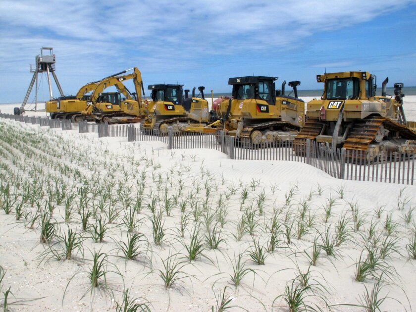 In this May 12, 2016 photo, heavy equipment carries out a beach replenishment project at the south end of Ocean City, N.J. A stormy winter chewed up New Jersey's beaches more than usual, necessitating greater efforts to restore them before the summer crowds hit the sand. (AP Photo/Wayne Parry)