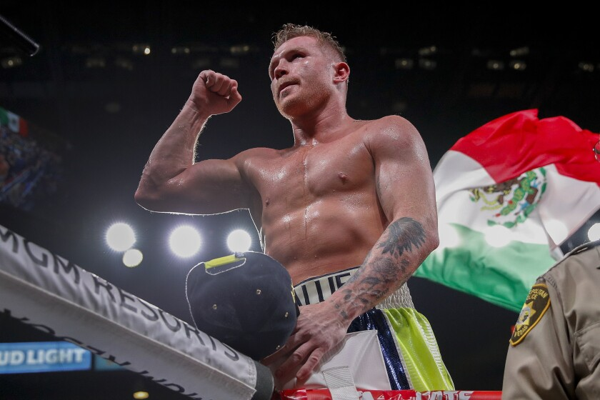 Canelo Alvarez, standing in the ring with a Mexican flag behind him, lifts a fist to make a muscle.
