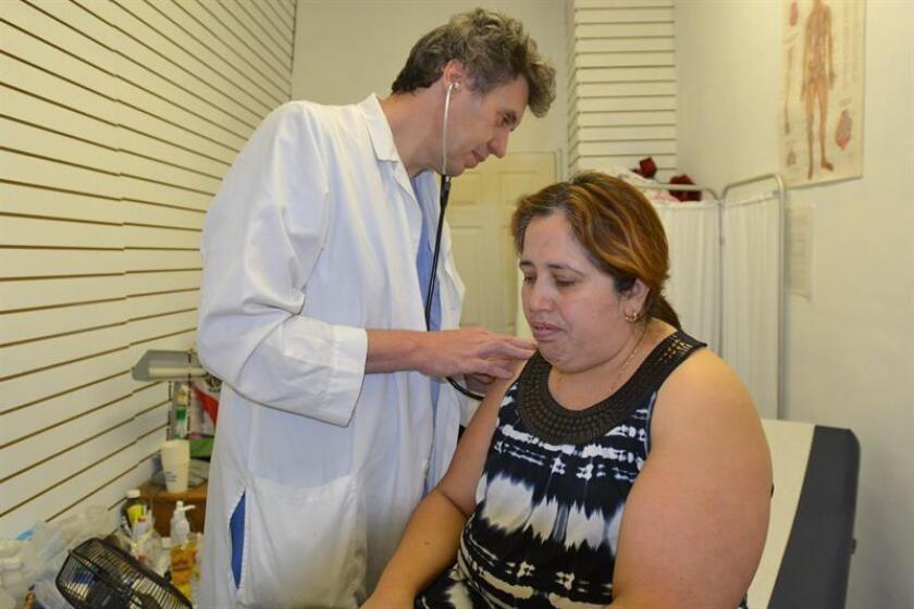 Vista de un médico que atiende a una paciente. EFE/Archivo