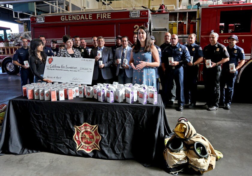 With Ashley Keehne and Kristina Guillen from the Coffee Bean & Tea Leaf at left, California Fire Foundation Director Elena Ruiz speaks about the help that will be provided to residents through the $31,000 donation from the coffee company at Glendale Fire Station 21 on Tuesday.