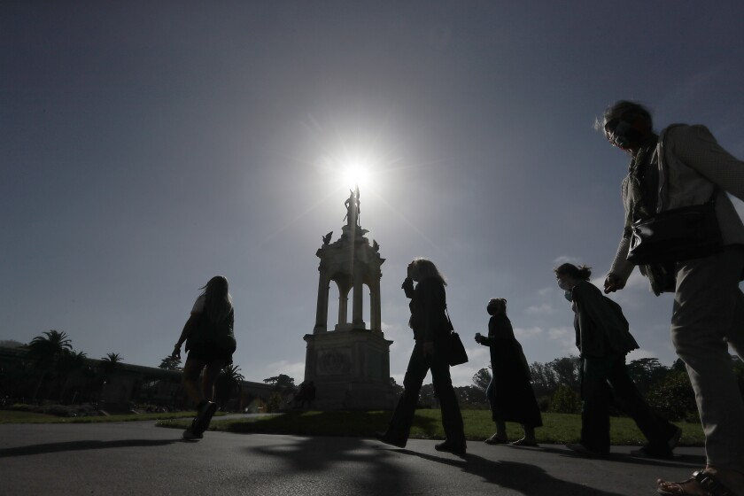 Visitors to Golden Gate Park in San Francisco wear protective masks on a sunny day.
