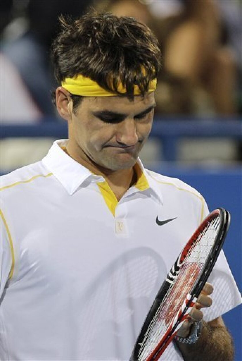 Roger Federer from Switzerland reacts after he lost a point to Rafael Nadal from Spain during the final match of the Mubadala World Tennis Championships in Abu Dhabi, United Arab Emirates, Saturday Jan.1, 2011. (AP Photo/Kamran Jebreili)