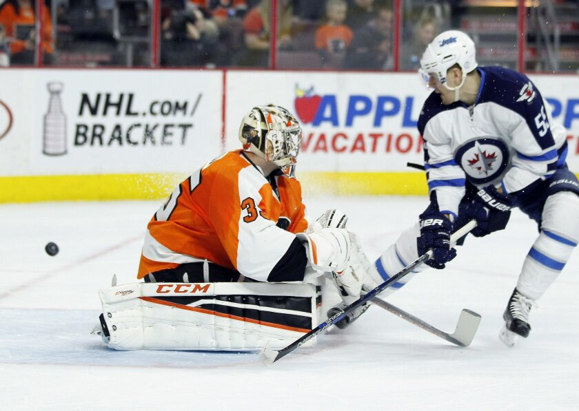 The puck goes wide of the net as Philadelphia Flyers' Steve Mason, left, fends off Winnipeg Jets' Mark Scheifele, right, during the first period of an NHL hockey game, Monday, March 28, 2016 in Philadelphia. (AP Photo/Tom Mihalek)