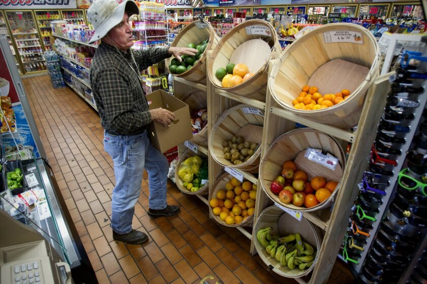 At Eagle Liquor Market in Chula Vista, Steve White restocks a basket with fresh avocados from his farm in Ramona. The goal is to make sure healthy food options are available. Nelvin C. Cepeda • U-T