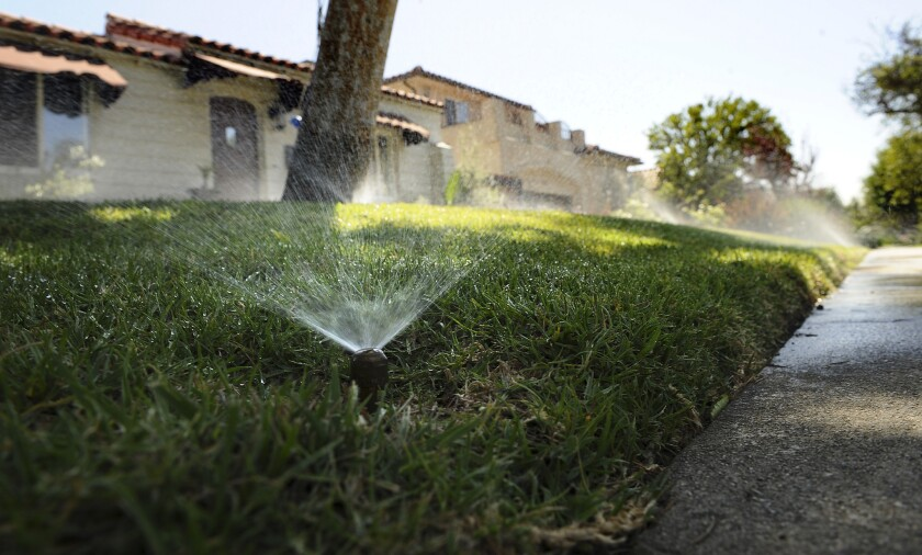 Sprinklers water a lawn at a West L.A. residence on April 17.