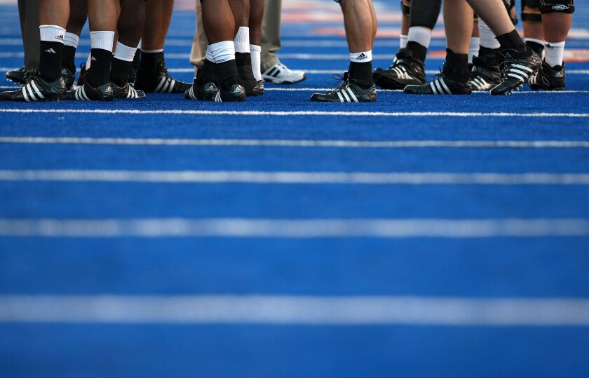 A view of players' cleats on Boise State's blue turf. Boise State and the Mountain West have been fighting over whether the school should continue to receive a bonus from the conference's future TV contracts.