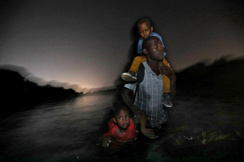 A Haitian man, with two children in tow, wades across the Rio Grande to Del Rio, Texas.