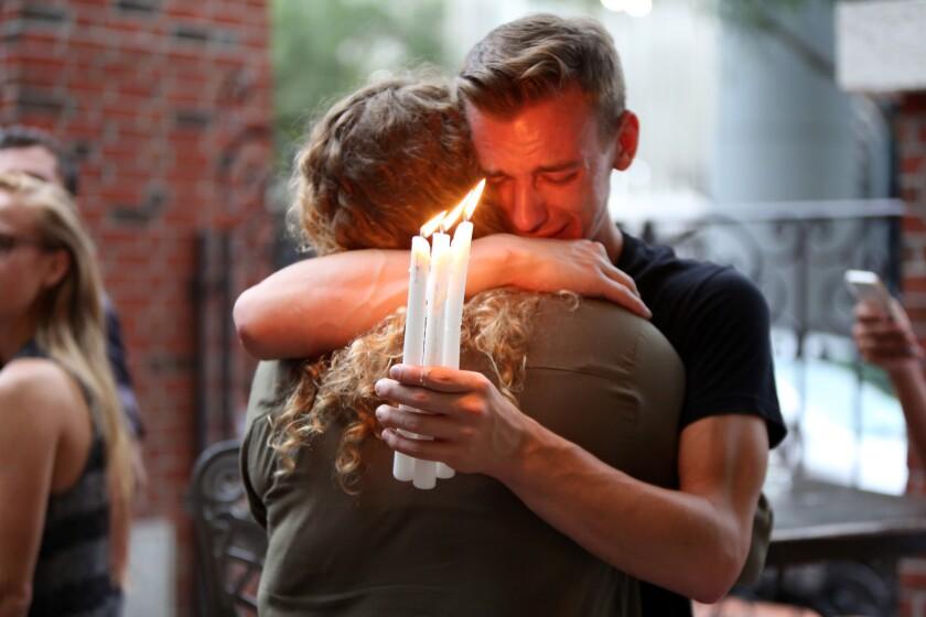 Brett Morian, de Daytona Beach, abraza a otro asistente a una vigilia en Ember por las 50 víctimas mortales de una balacera en un club nocturno gay de Orlando, el 12 de junio de 2016. (Joshua Lim/Orlando Sentinel via AP)