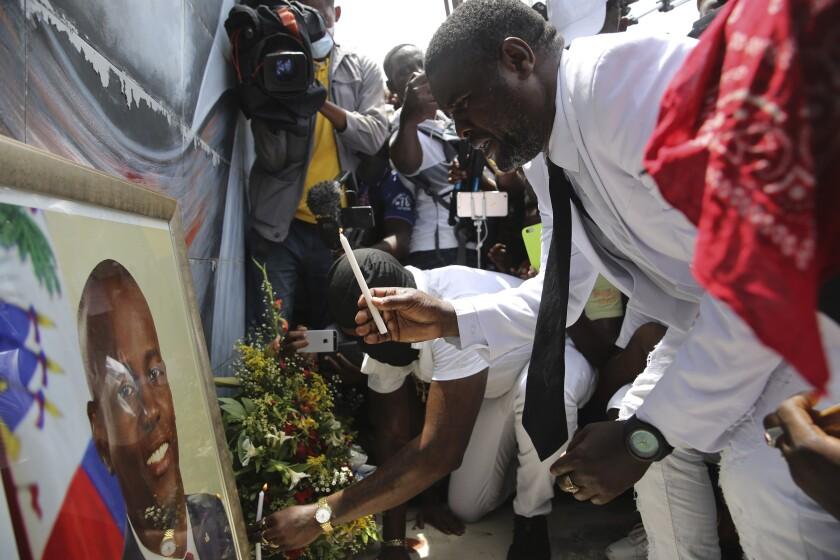 """Jimmy """"Barbecue"""" Cherizier, un expolicía que dirige una coalición de bandas criminales llamada """"G9"""", enciende una vela frente a un retrato del presidente asesinado Jovenel Moïse durante una manifestación el lunes 26 de julio de 2021 para exigir justicia, en Puerto Príncipe, Haití. (AP Foto/Joseph Odelyn)"""